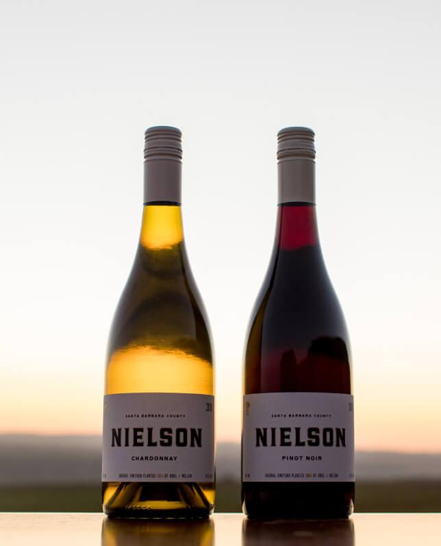 A bottle of Nielson Chardonnay and Pinot Noir against a sunset