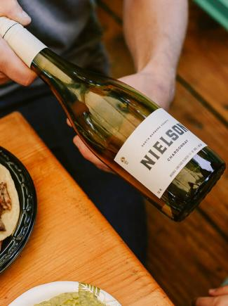 Nielson Chardonnay bottle being held next to food